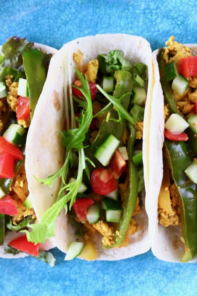 Three tacos filled with scrambled tofu, green peppers and chopped cucumber and tomatoes on a blue plate