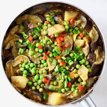 Aubergine, potato and pea curry in a round pan against a white background
