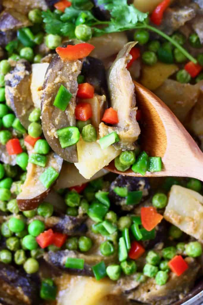 Aubergine, potato and pea curry in a pan with a wooden spoon lifting up a mouthful