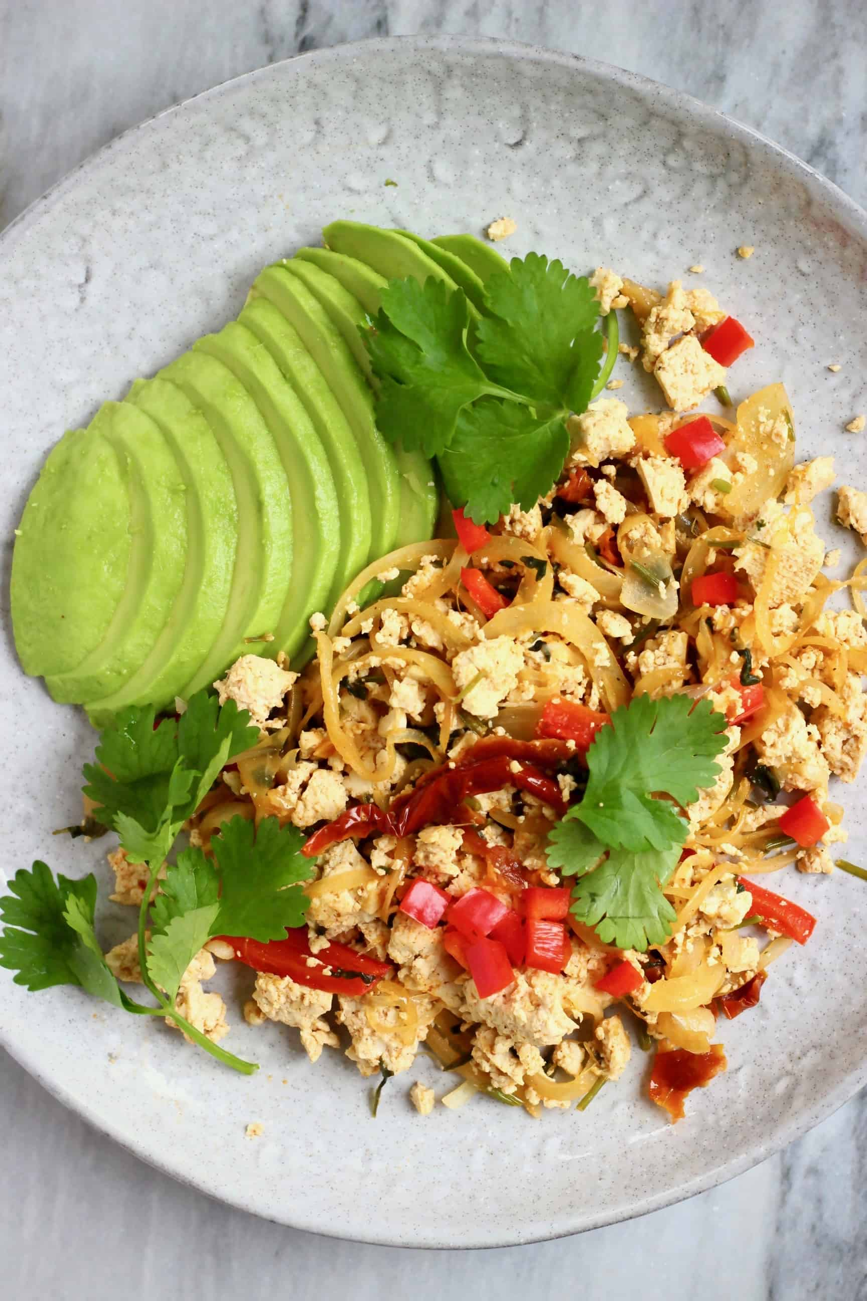 Scrambled tofu with red peppers and a sliced avocado on a grey plate against a marble background