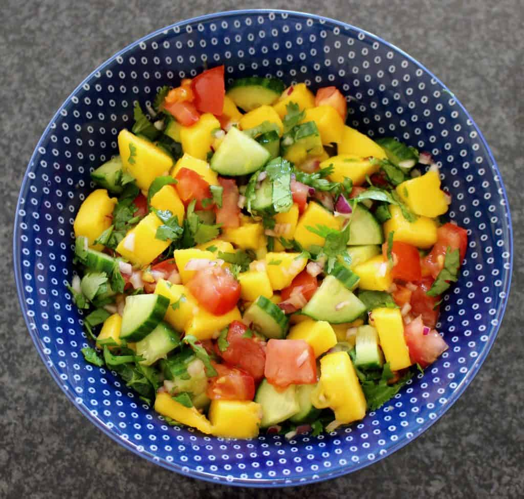 Chopped mango, tomatoes, cucumber and coriander in a blue bowl against a granite background