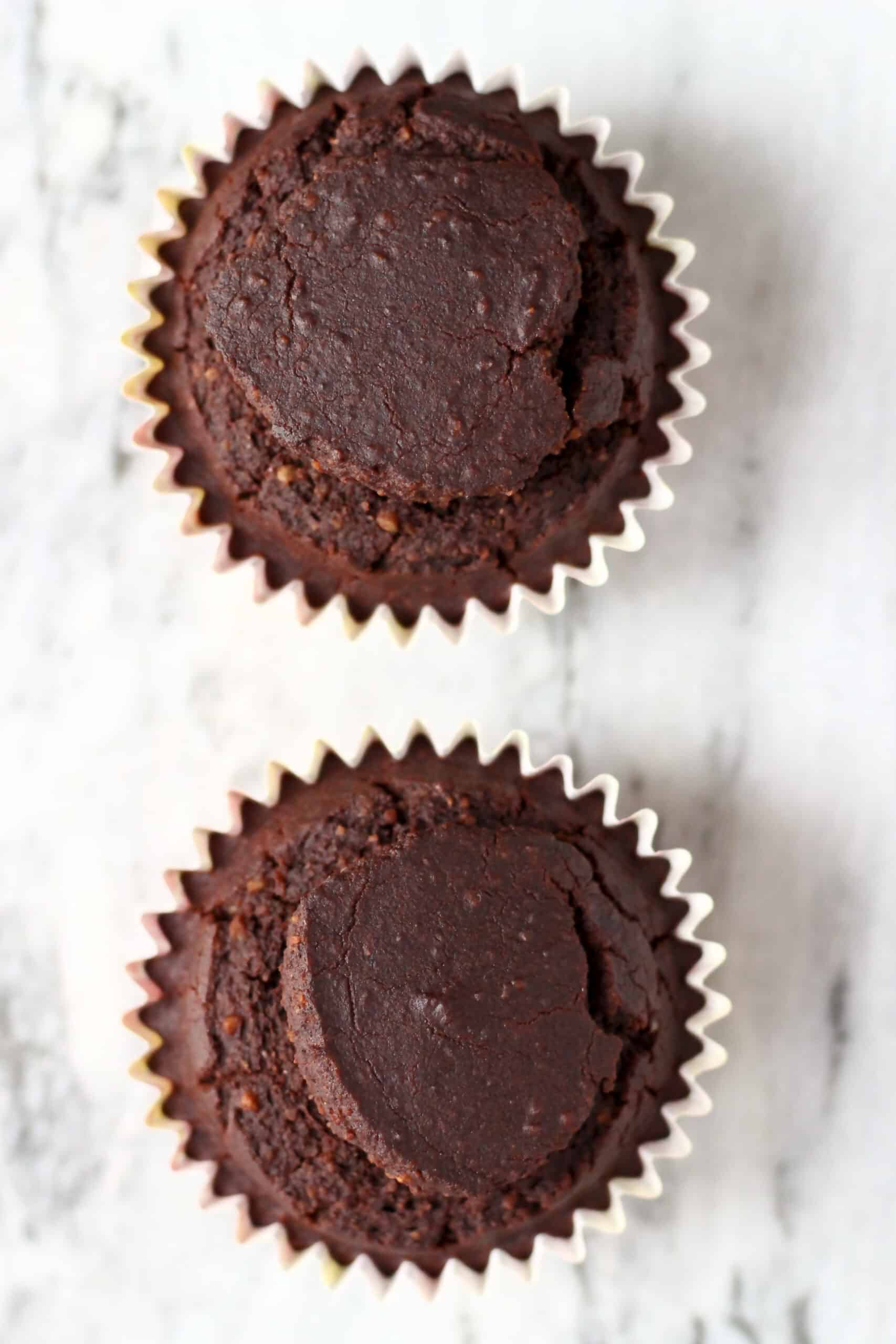 Two baked gluten-free vegan chocolate cupcakes in cupcake cases