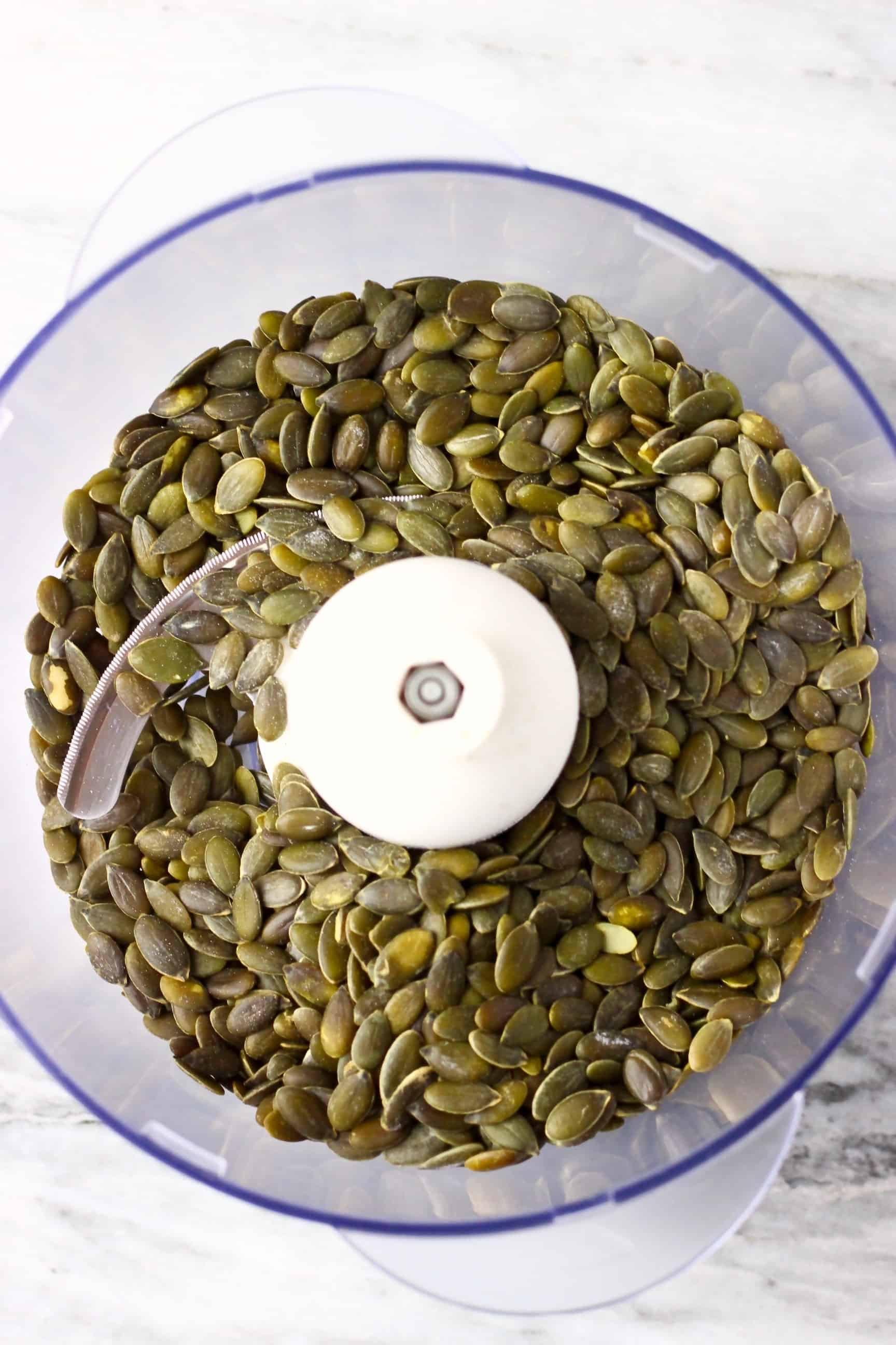Pumpkin seeds in a food processor against a marble background