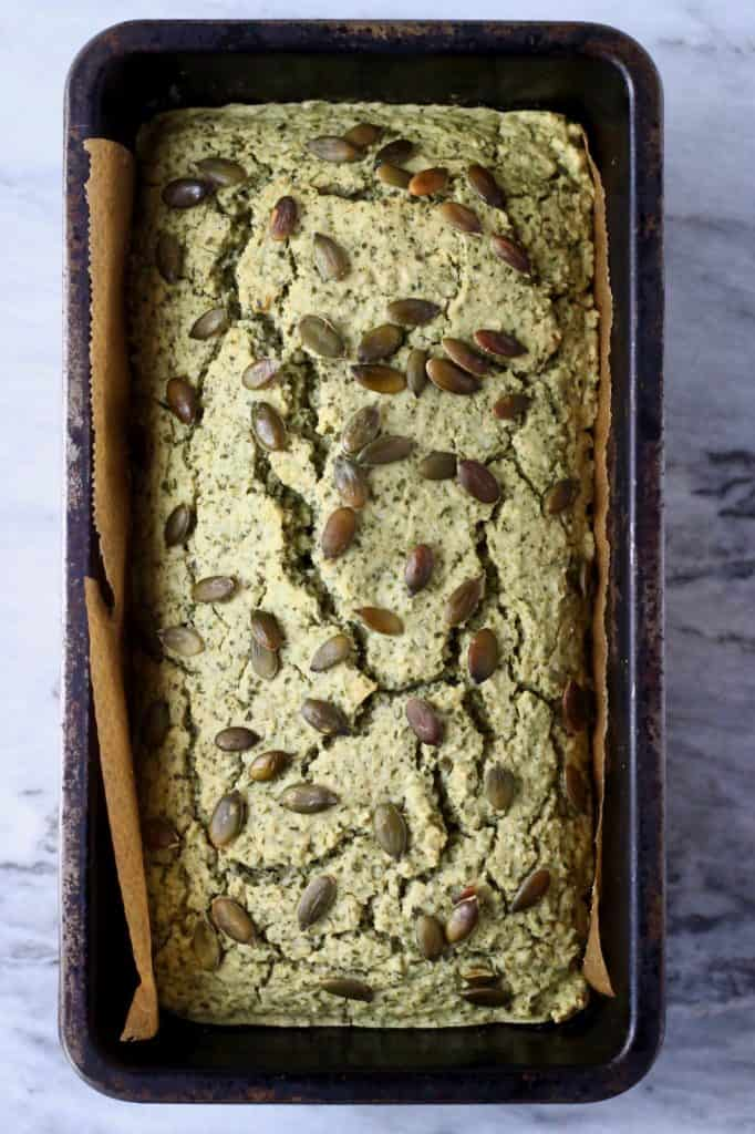 A loaf of pumpkin seed bread topped with pumpkin seeds in a black loaf tin against a marble background
