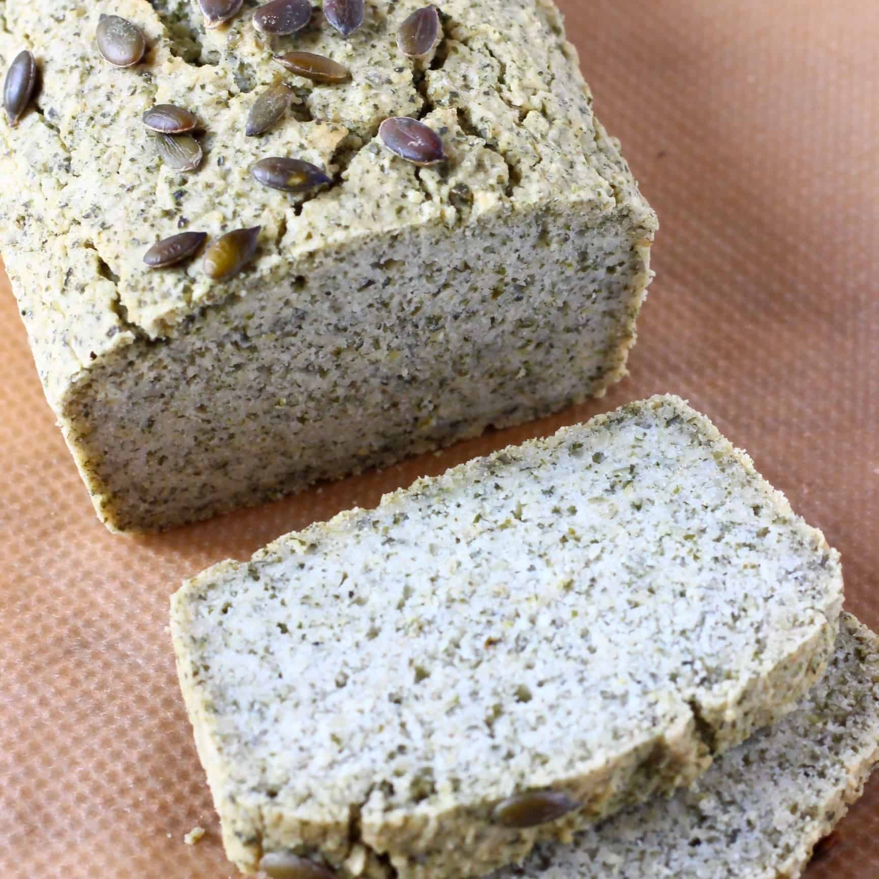 A loaf of pumpkin seed bread with two slices next to it against a sheet of brown baking paper