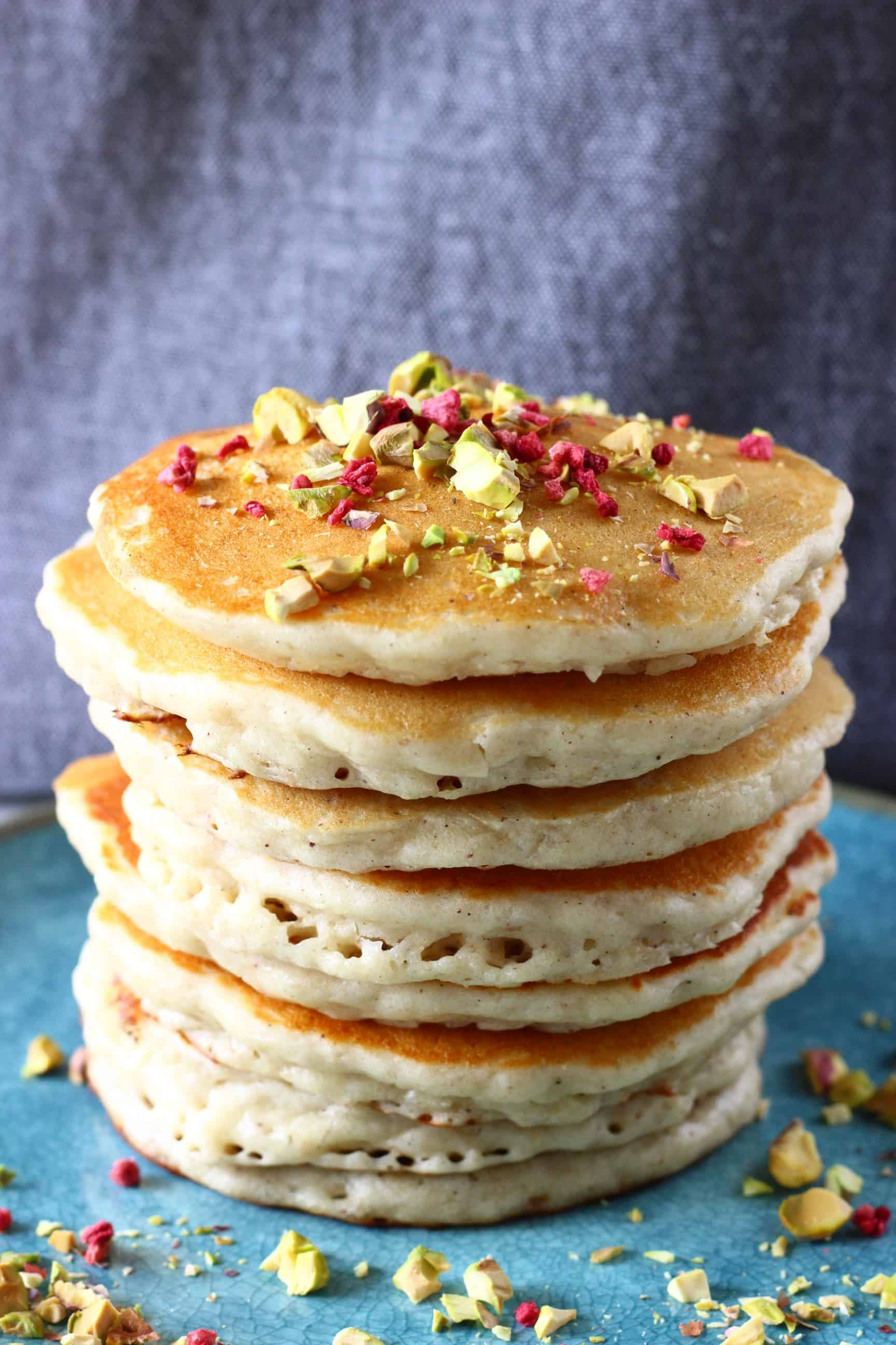 A stack of gluten-free vegan oatmeal pancakes on a plate sprinkled with chopped pistachios and freeze-dried raspberries
