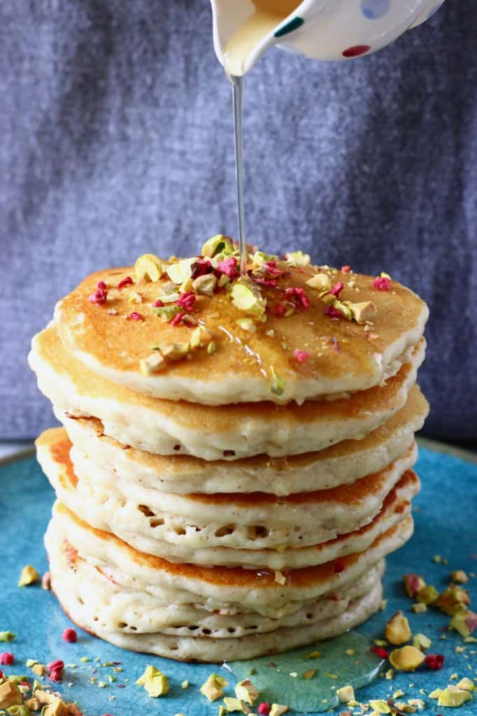 A stack of oatmeal pancakes on a blue plate against a grey background with syrup being poured over the top in a small spotted jug
