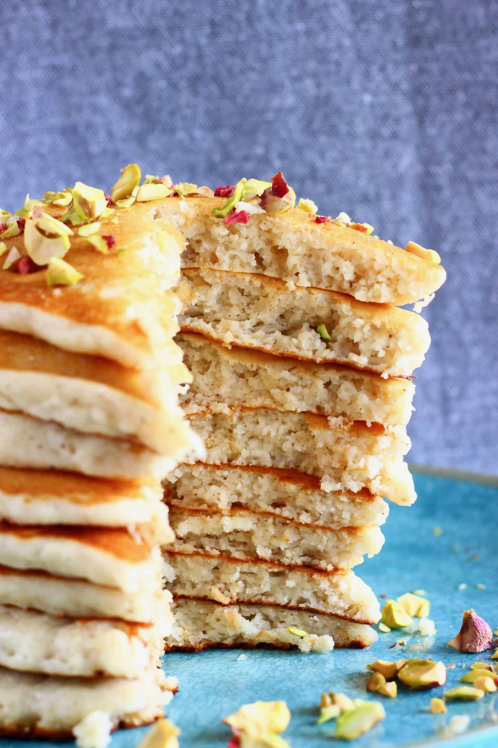 A stack of sliced gluten-free vegan oatmeal pancakes on a plate topped with chopped pistachios