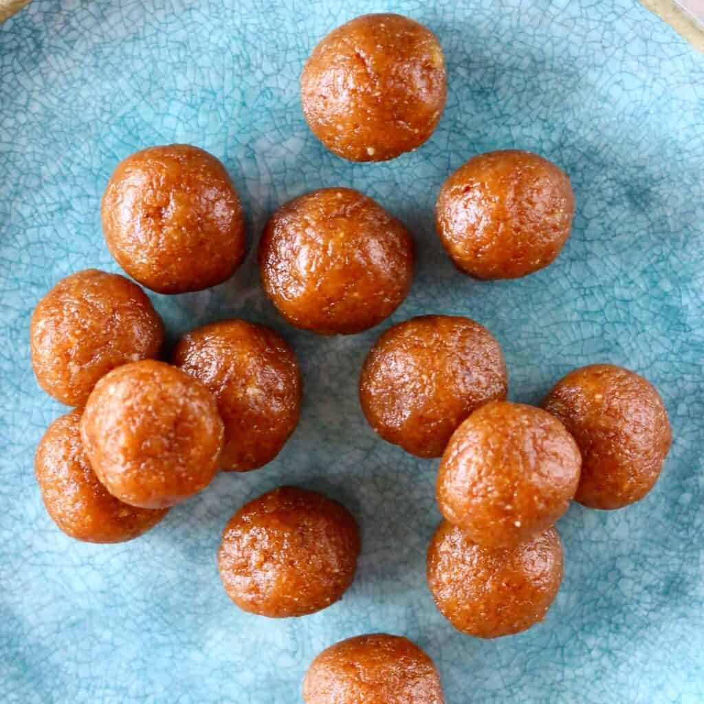 Lots of brown round energy balls on a blue plate