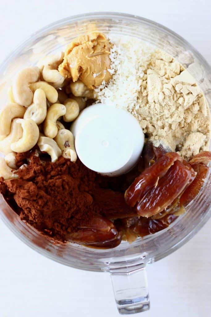 Dates, cashews, almond buter, desiccated coconut, cocoa powder and protein powder in a food processor against a white background