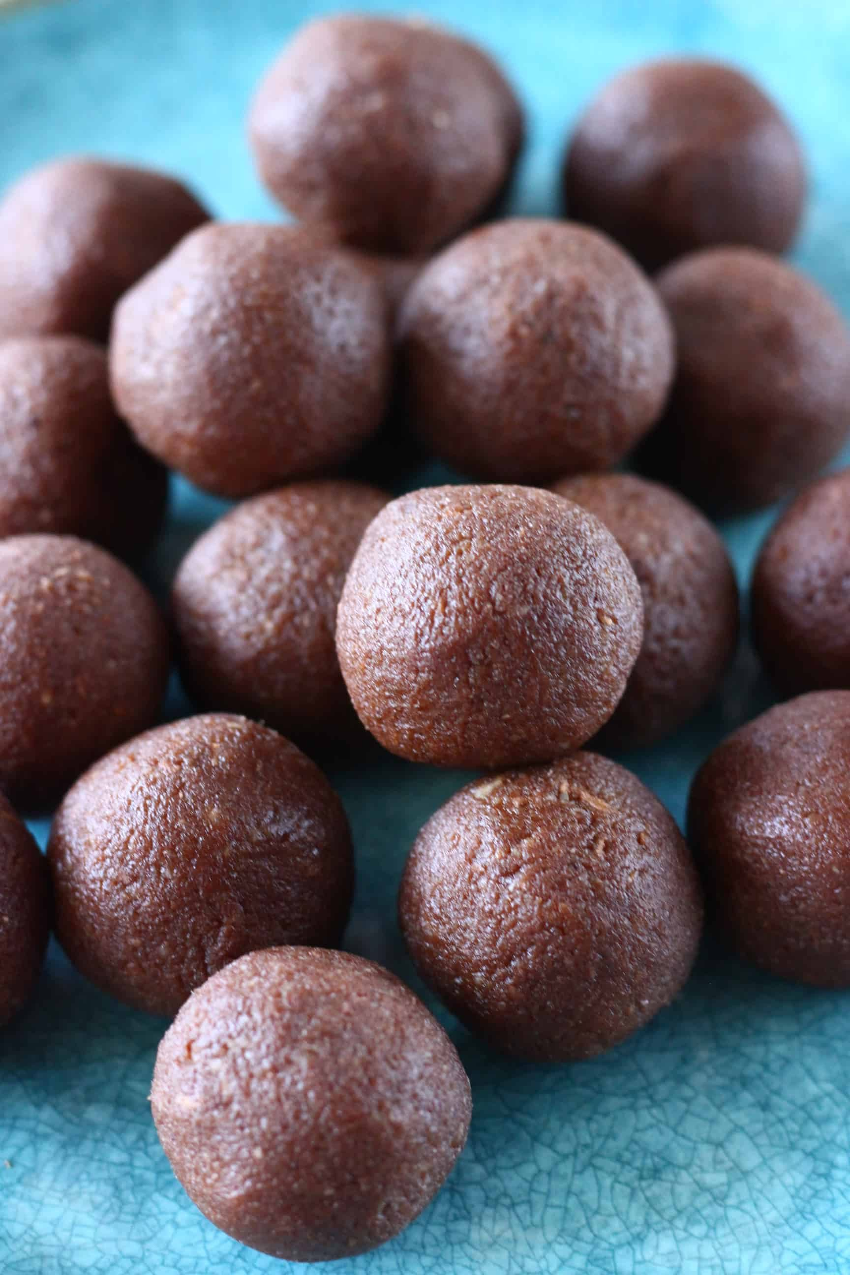 A pile of chocolate vegan protein balls on a blue plate