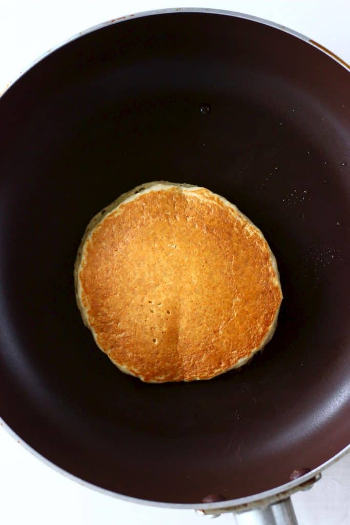 A golden brown pancake being cooked in a black frying pan against a marble background
