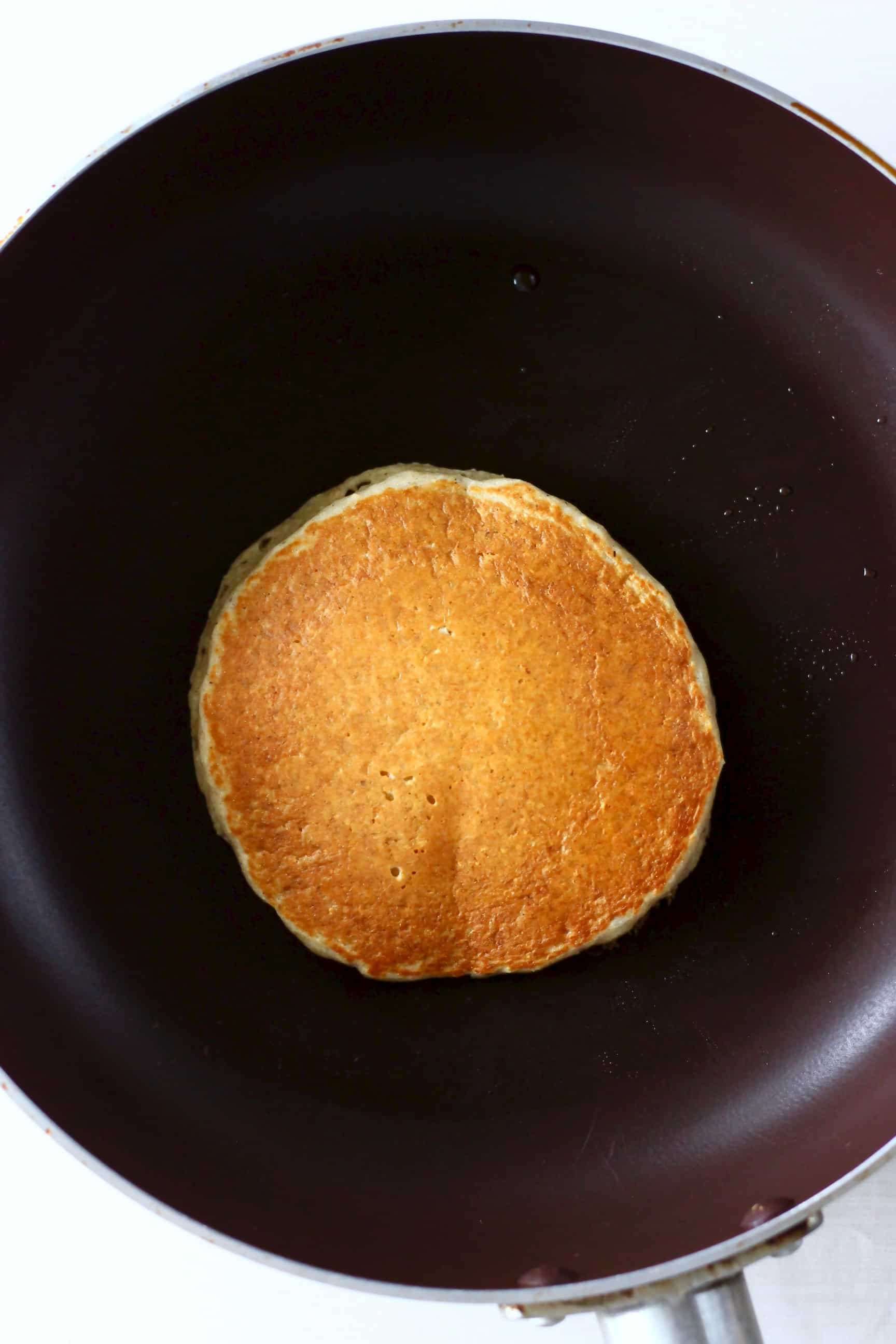 A golden brown oat flour pancake being cooked in a black frying pan against a marble background