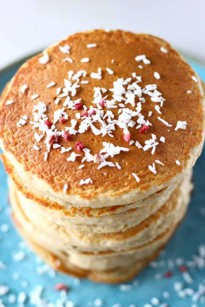 A stack of golden brown pancakes topped with desiccated coconut on a blue plate