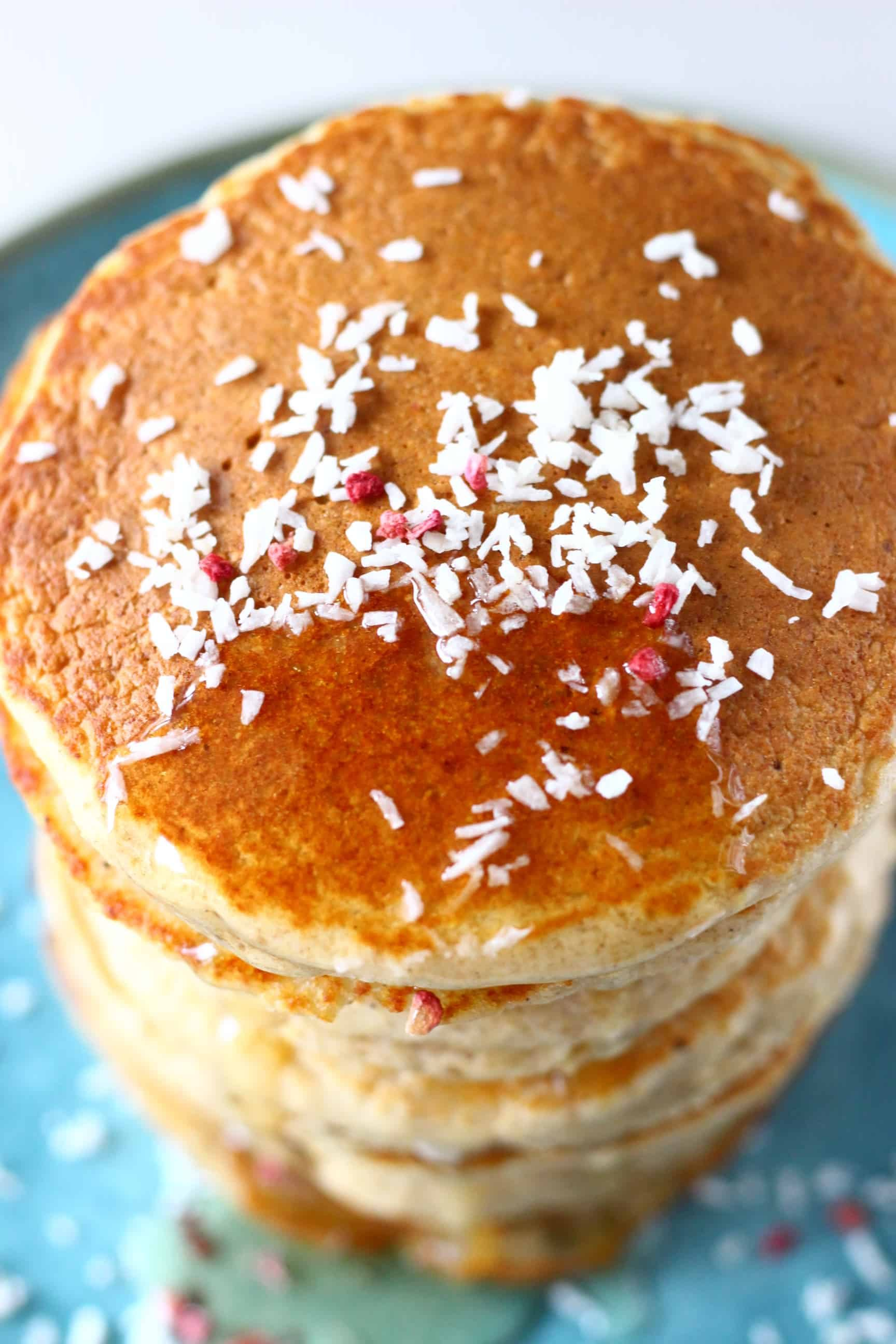 A stack of oat flour pancakes topped with desiccated coconut and syrup on a blue plate