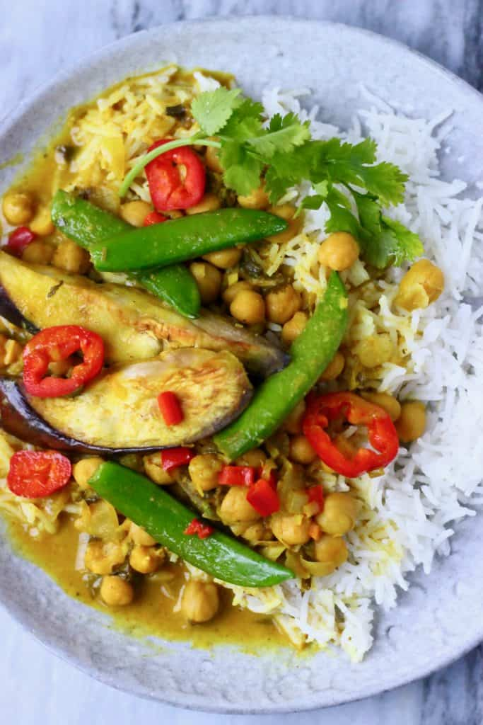Eggplant, chickpea and vegetable curry with white rice on a grey plate against a marble background