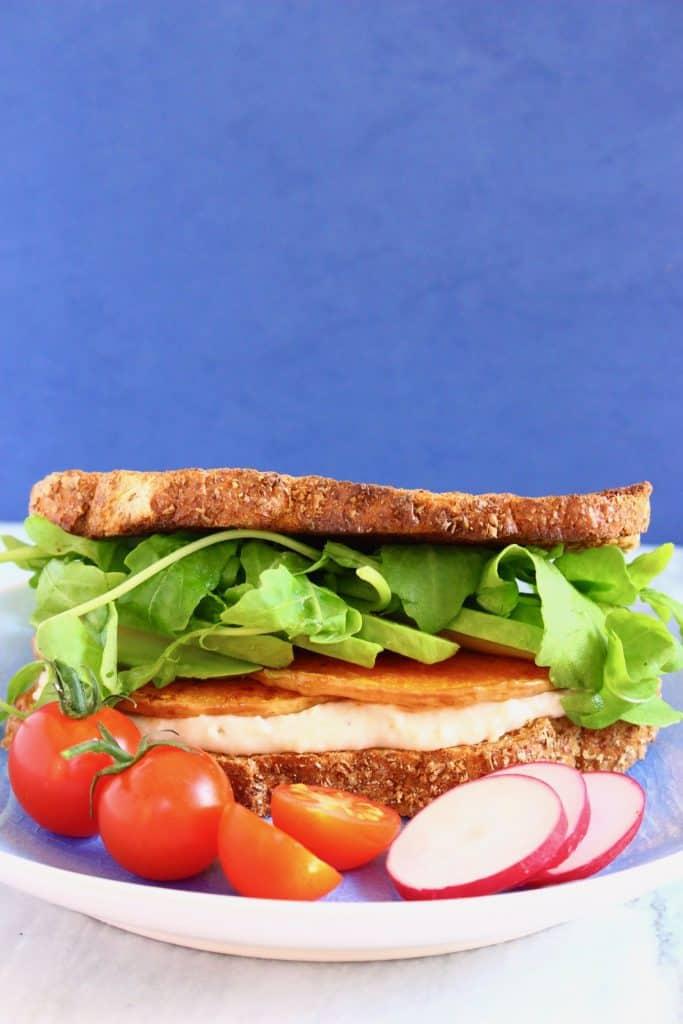 Hummus, butternut squash and lettuce sandwich on a light blue plate against a dark blue background
