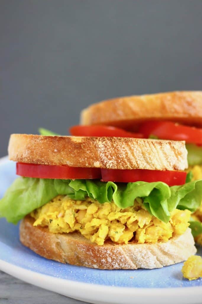 Yellow mashed chickpeas, lettuce and red pepper in sandwiches on a blue plate against a grey background