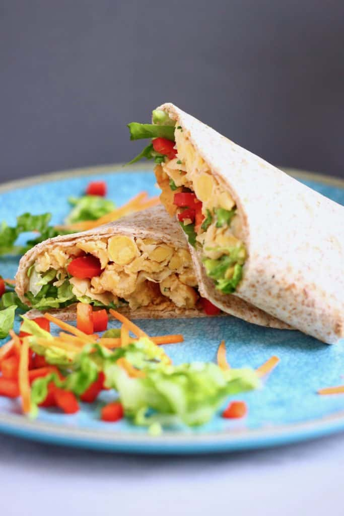 Two wraps filled with creamy chickpeas and salad on a blue plate against a grey background