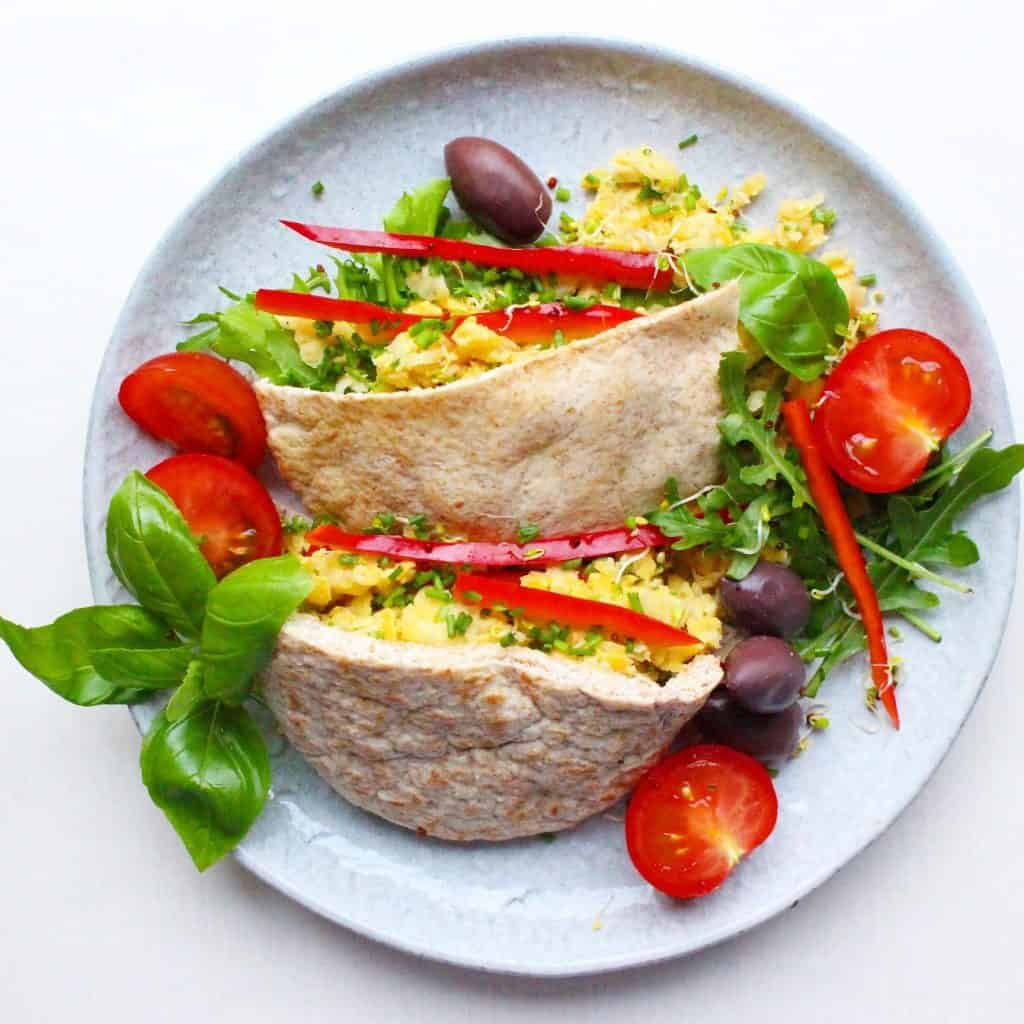 Two pitta halves filled with mashed chickpeas and salad on a grey plate against a white background