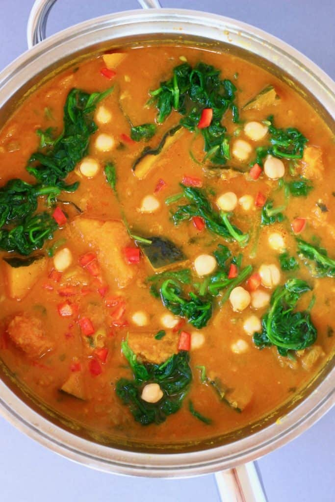 Diced pumpkin, chickpeas and spinach in a yellow curry sauce in a silver saucepan