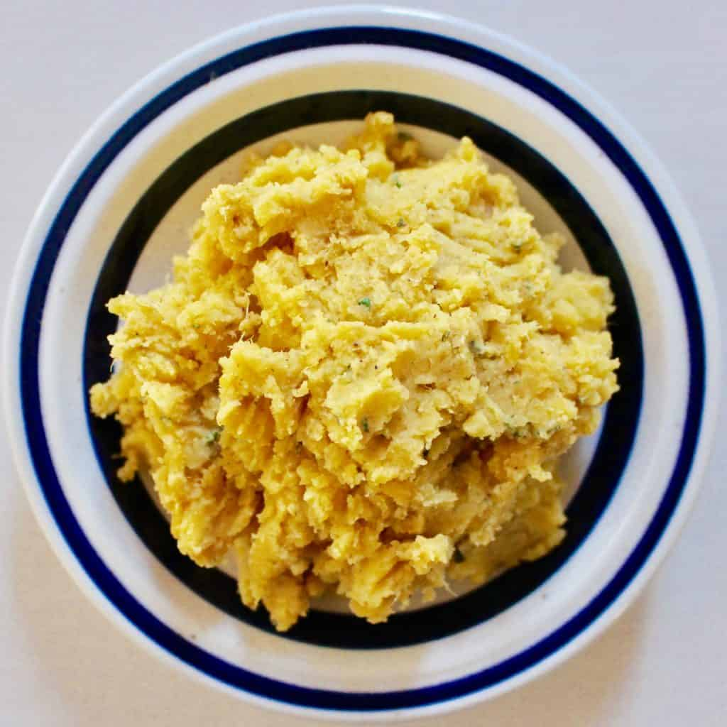 Photo of sweet potato hummus in a white bowl with a dark blue rim