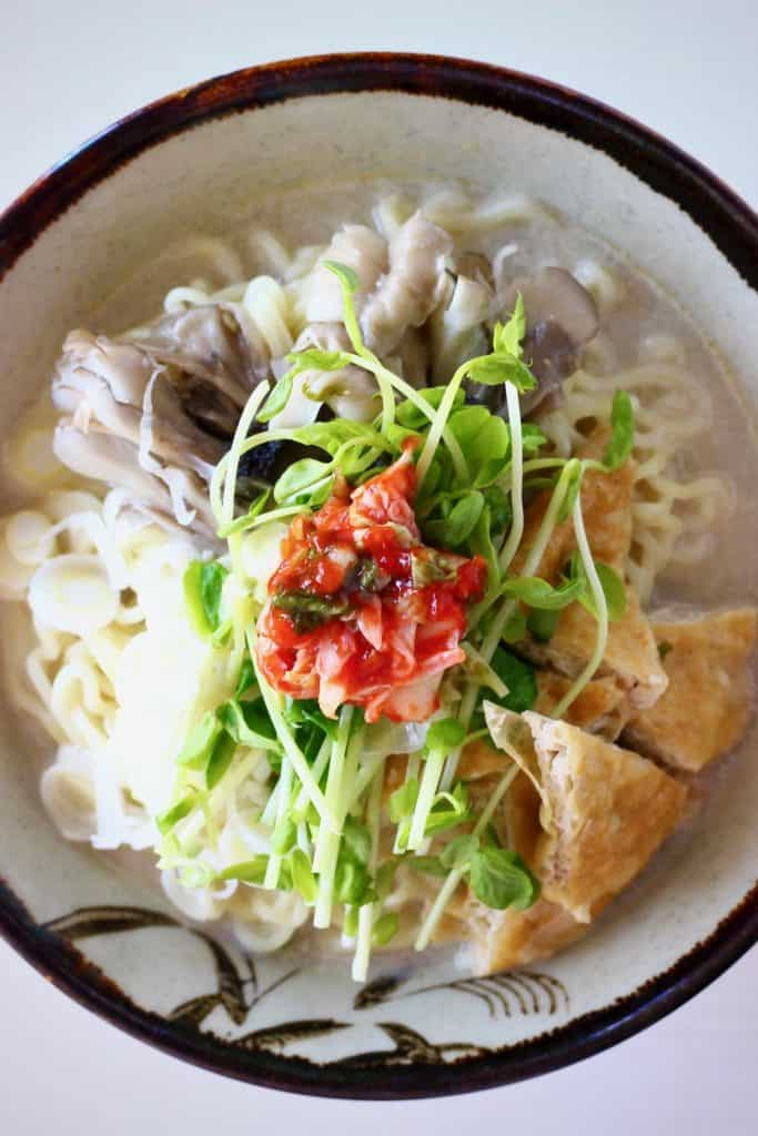 Soy milk ramen topped with pieces of tofu, mushrooms, greens and kimchi in a light brown bowl with a dark brown rim against a white background