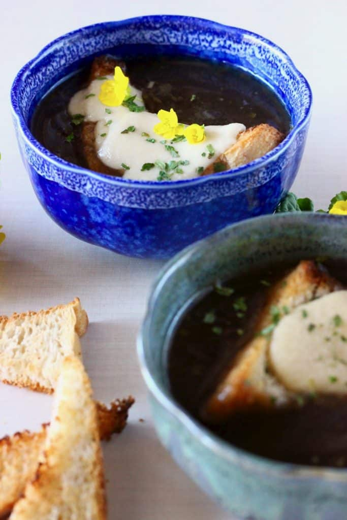 Two blue bowls of dark soup topped with cheesy toast against a white background