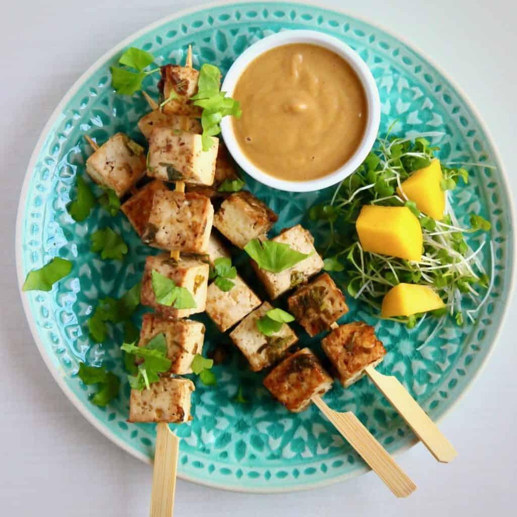 Three skewers with brown tofu cubes on a green plate with a light brown sauce in a white bowl