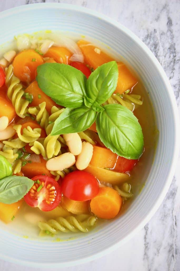 Pea pasta, white beans, fresh tomatoes and basil in a clear soup in a light blue bowl against a marble background