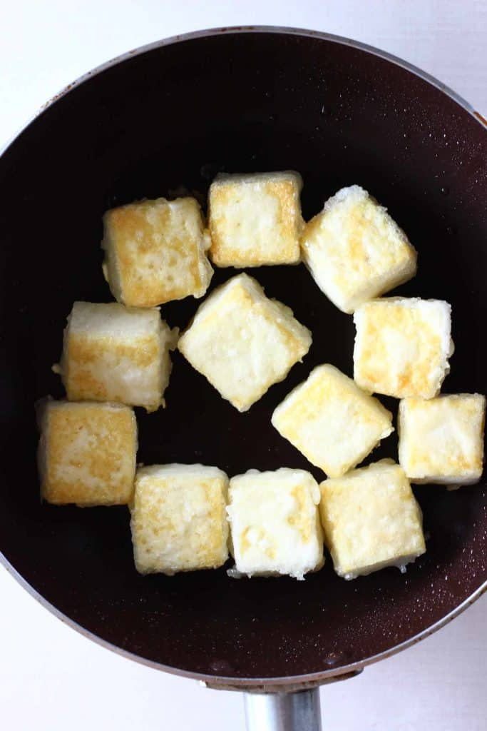 Golden brown cubes of tofu in a dark brown frying pan against a white background
