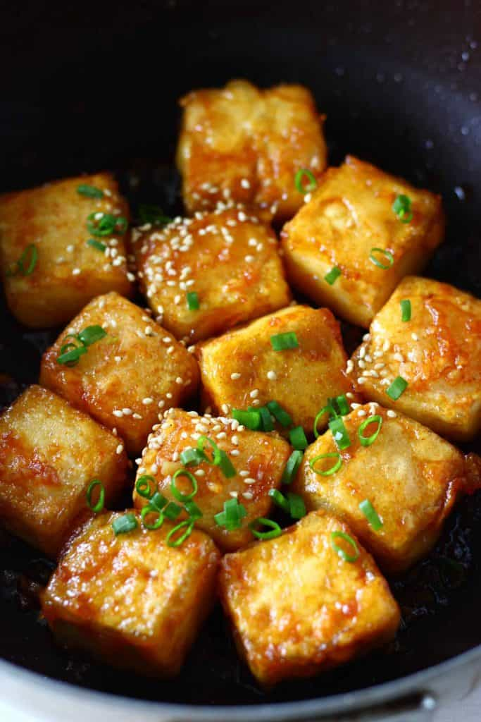 Cubes of tofu in a red sauce sprinkled with sesame seeds and sliced spring onions in a black frying pan