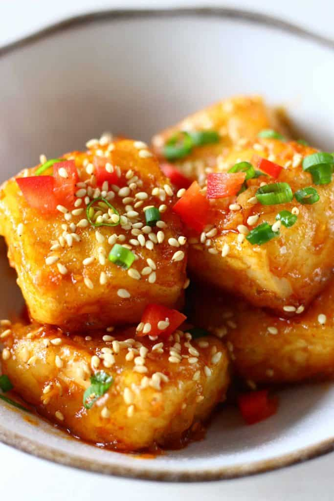 Cubes of tofu in a red sauce sprinkled with sesame seeds, sliced spring onions and chilli in a white bowl with a brown rim against a white background