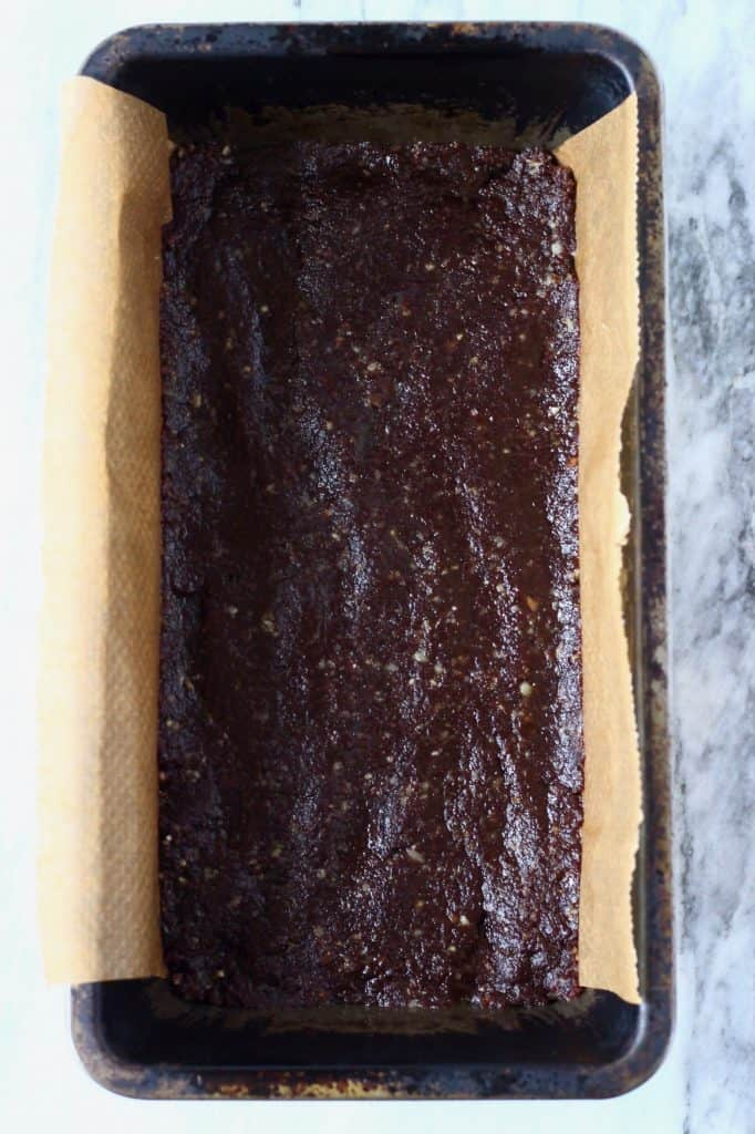 Raw chocolate brownie mixture in a black loaf tin lined with brown baking paper against a marble background