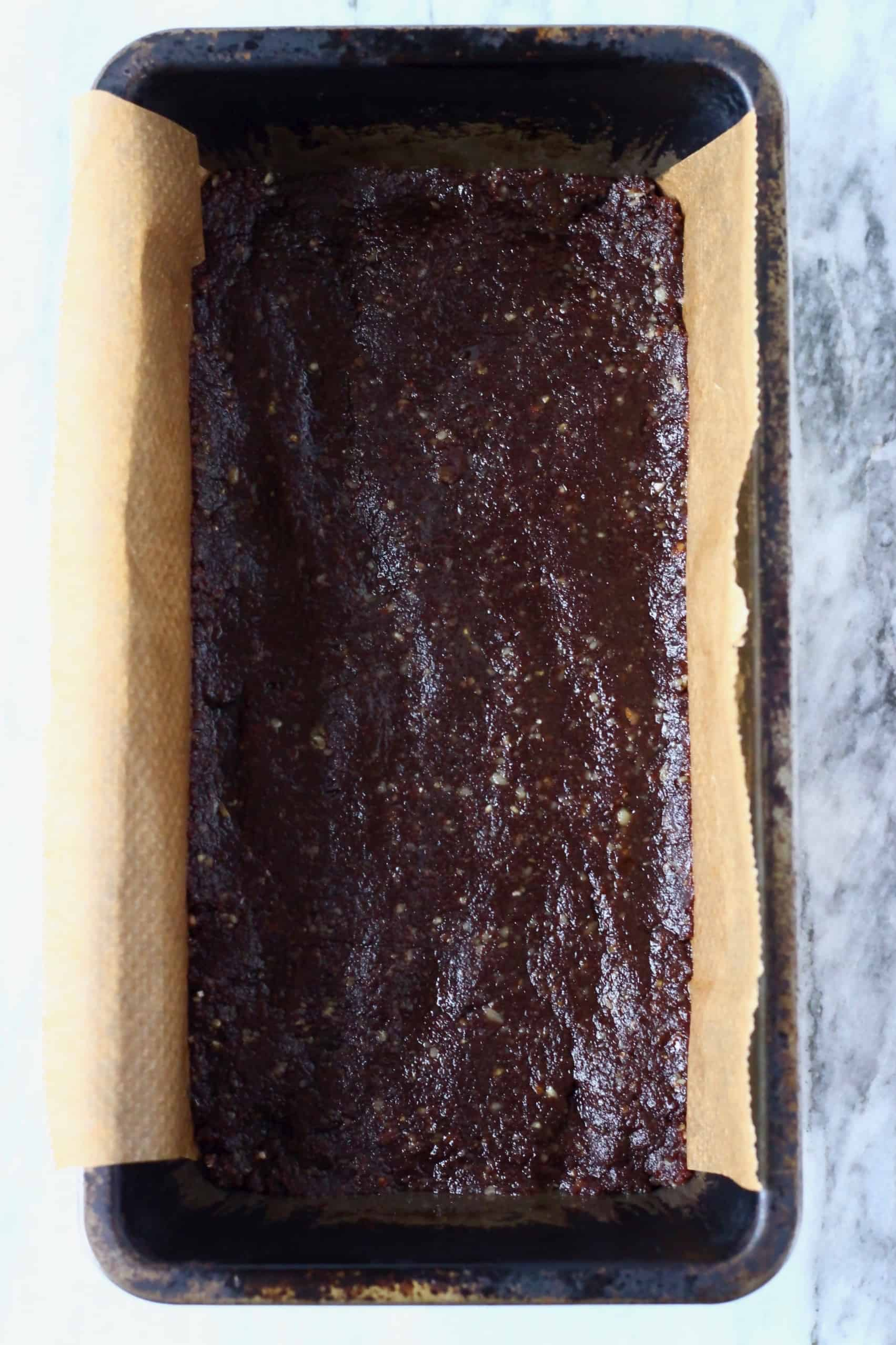 Chocolate no-bake vegan brownie mixture in a loaf tin lined with baking paper