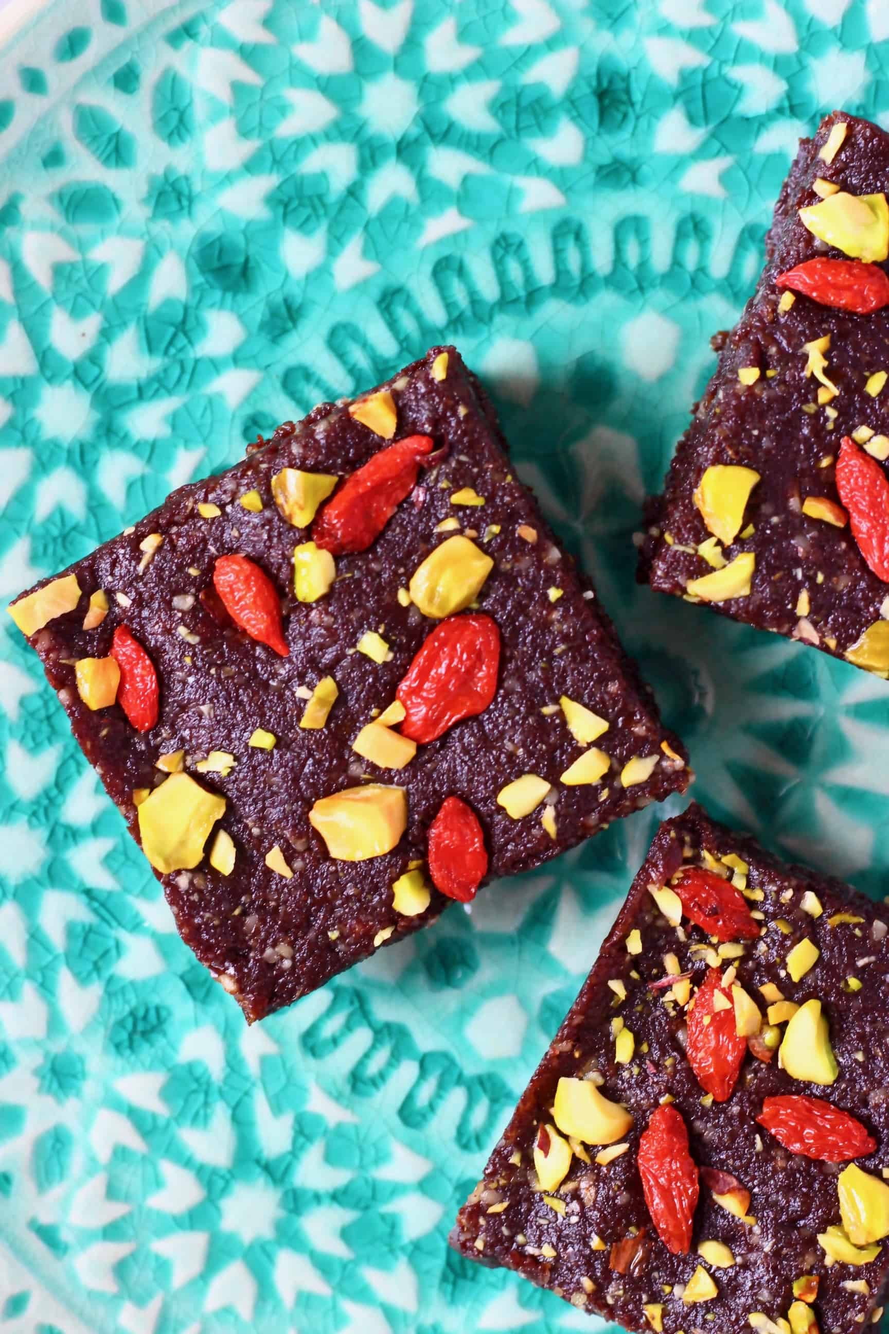 Three square no-bake vegan brownies topped with goji berries and chopped pistachios on a plate