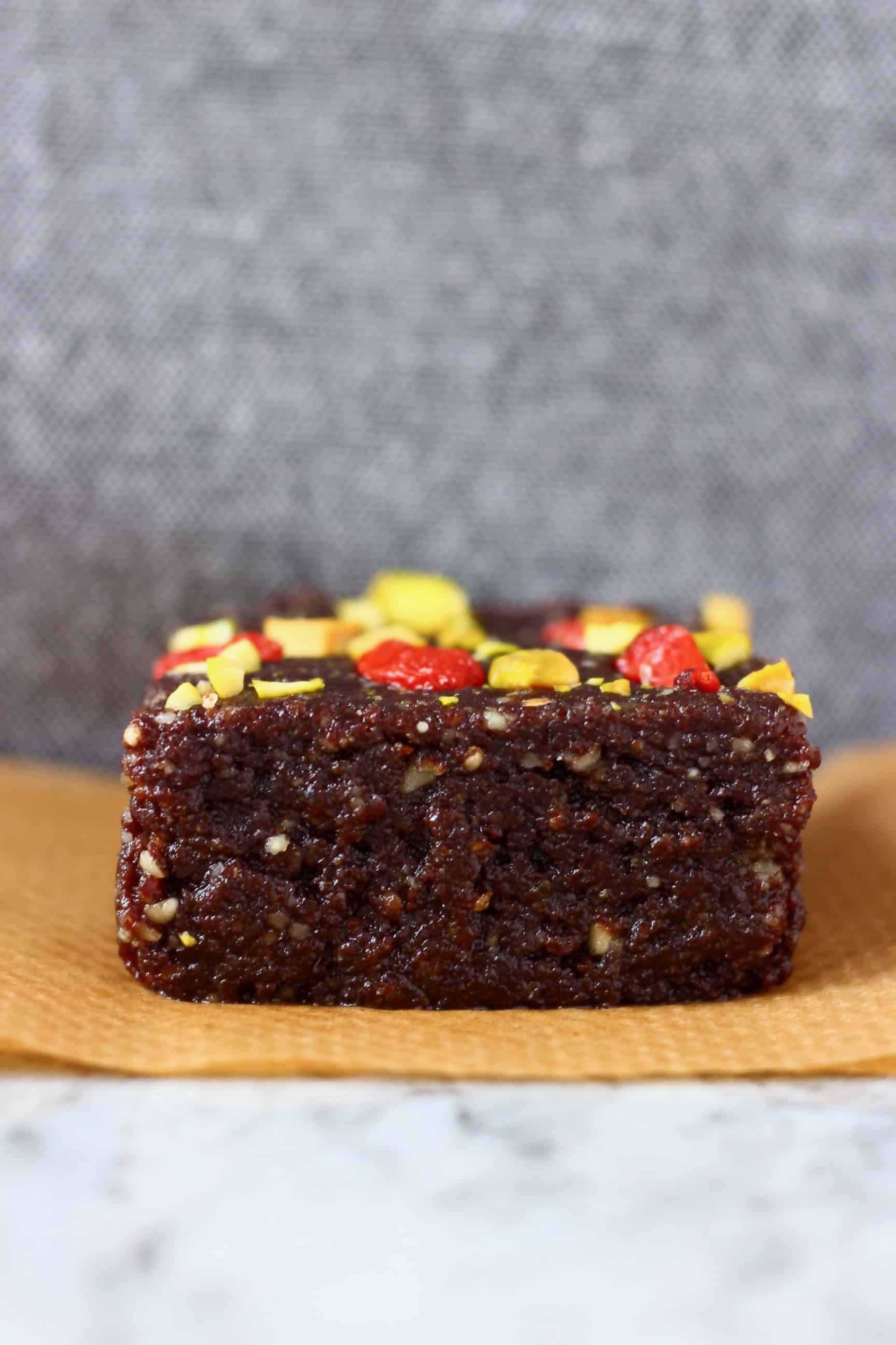A square no-bake vegan brownie topped with goji berries and chopped pistachios on a piece of baking paper