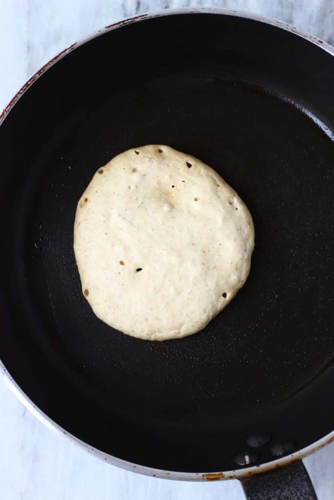 A raw white pancake being cooked in a black frying pan against a marble background