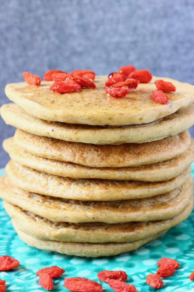 A stack of banana oatmeal pancakes decorated with goji berries on a green plate against a grey background