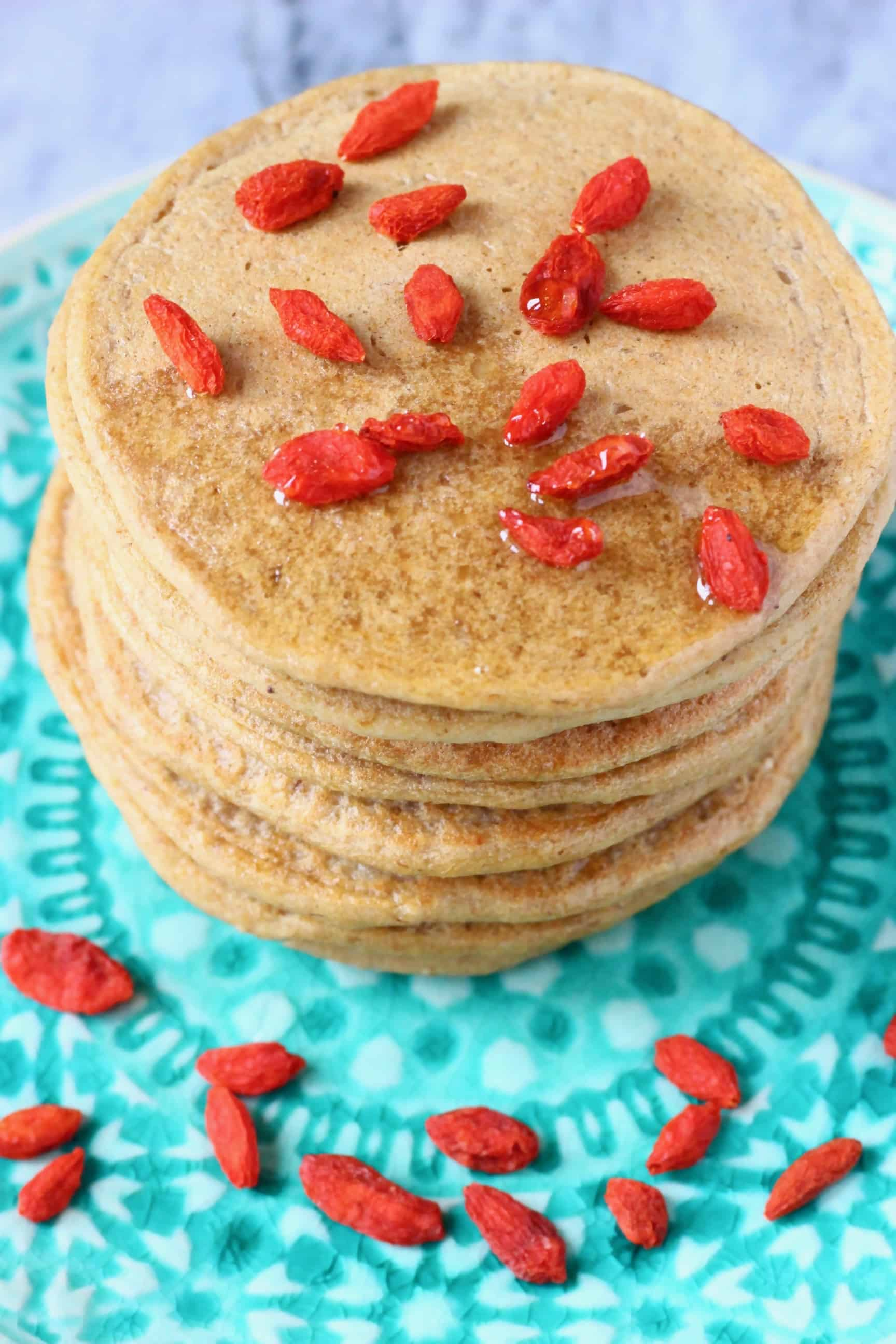 A stack of banana oatmeal pancakes decorated with goji berries on a green plate against a marble background