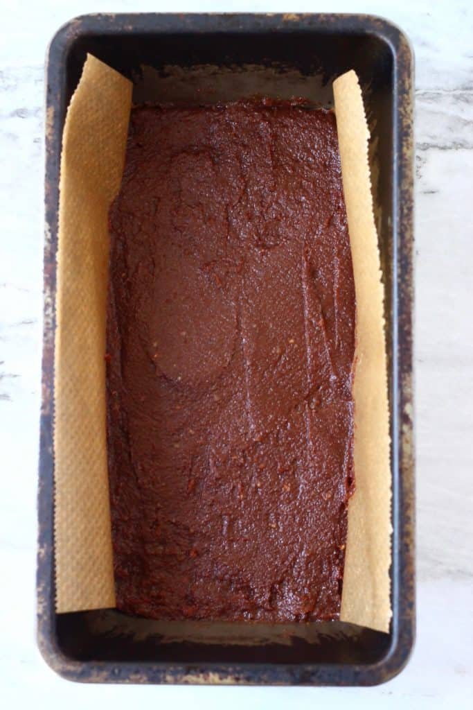 Chocolate bar mixture in a black loaf tin lined with brown baking paper against a marble background