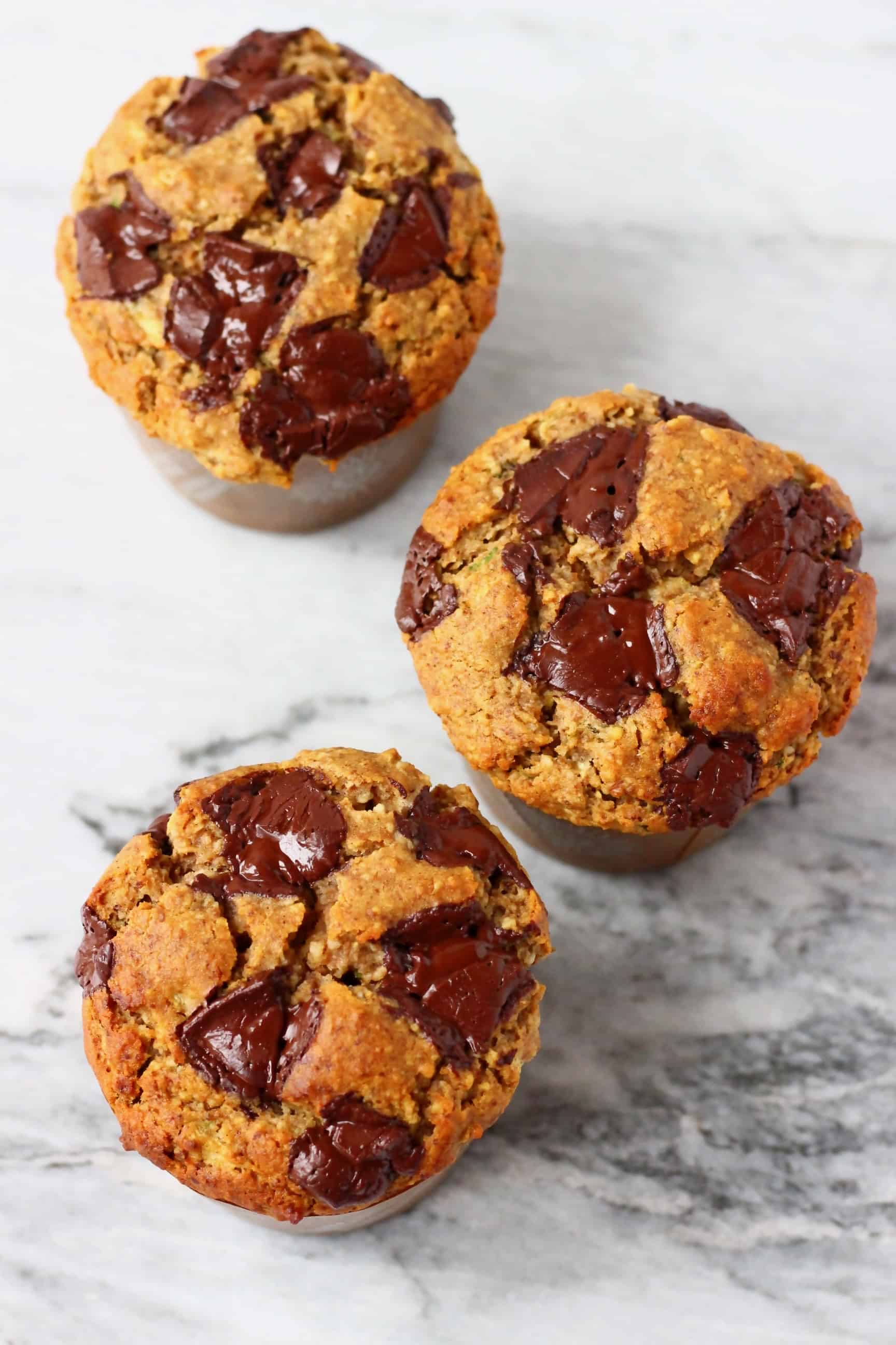 Three zucchini muffins with chocolate chips against a marble background