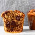 A gluten-free vegan zucchini muffin with chocolate chips cut in half on a marble slab against a grey background