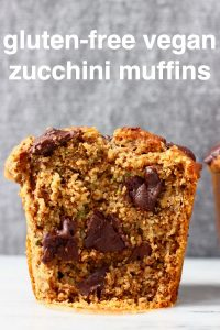 A zucchini muffin with chocolate chips cut in half on a marble slab against a grey background