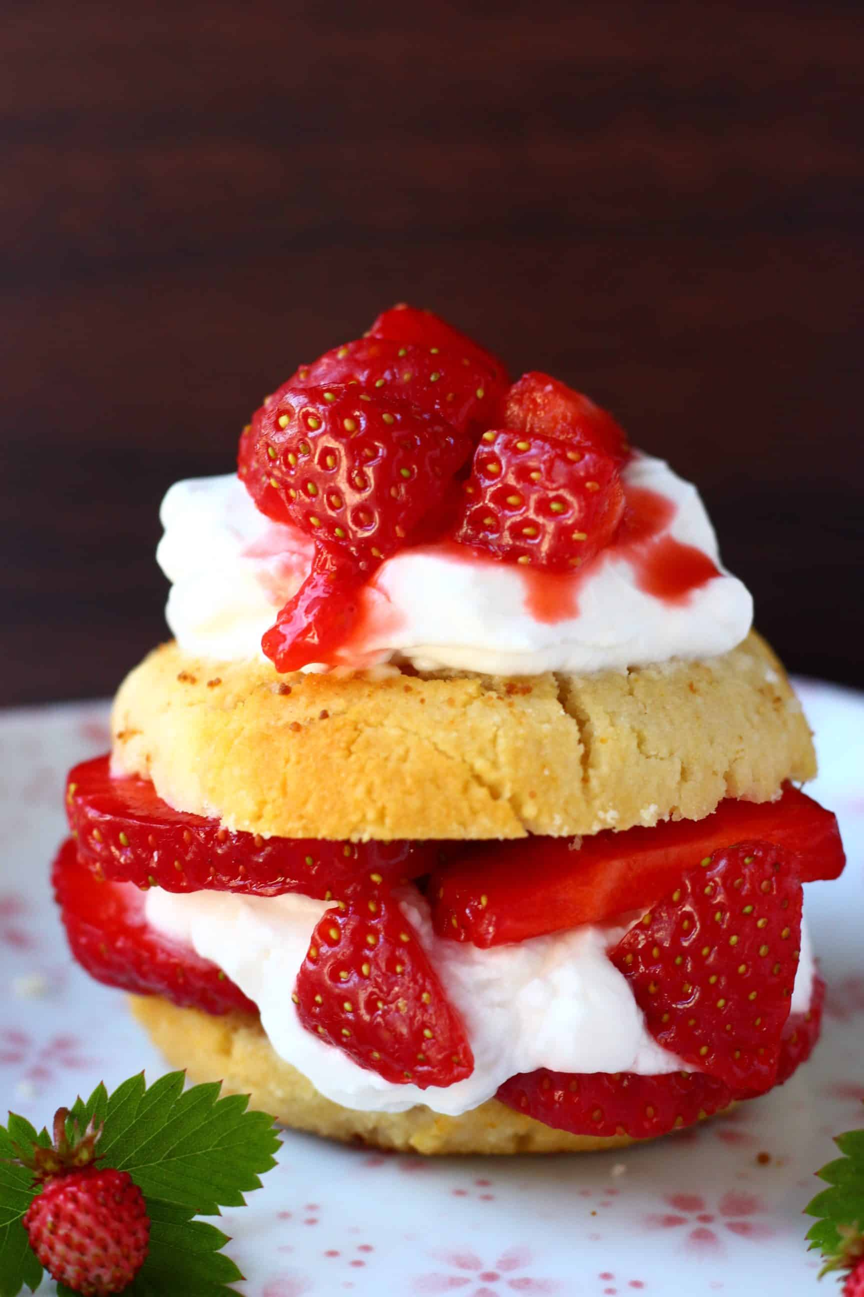 A gluten-free vegan strawberry shortcake sandwiched with coconut whipped cream and fresh strawberries on a plate