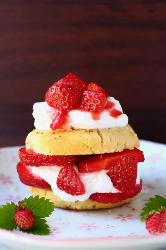 A strawberry shortcake sandwiched with coconut whipped cream and fresh strawberries on a white plate decorated with pink flowers against a dark brown background