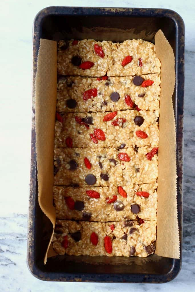 Raw granola bar mixture with chocolate chips and goji berries cut into six bars in a black loaf tin lined with brown baking paper against a marble background