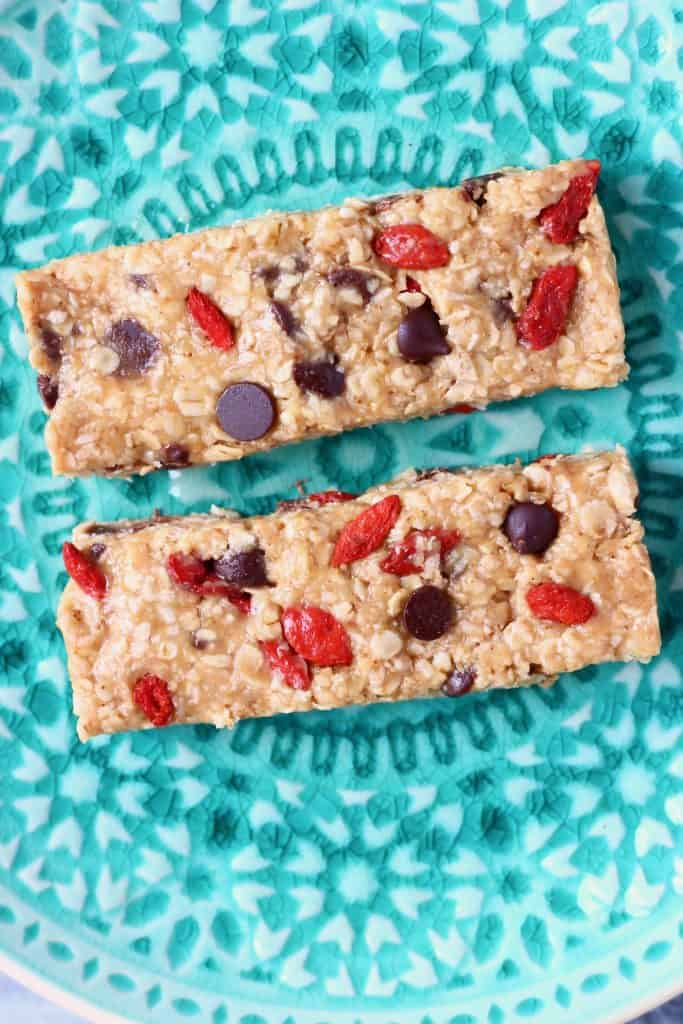 Two light brown granola bars studded with chocolate chips and goji berries on a green plate
