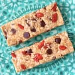 Two no-bake granola bars studded with chocolate chips and goji berries on a green plate