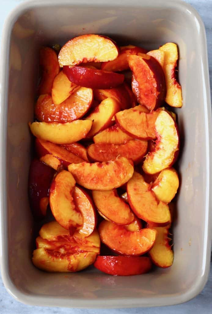 Sliced peaches in a rectangular grey baking dish